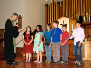 Rev. Tom Kinder presenting Bibles to the older children