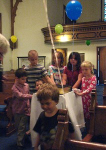 The children roll the Bible to the front of the sanctuary